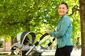 Hispanic Mom Pushing Her Baby In A Stroller. poster