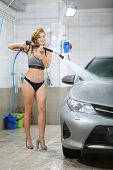 Smiling girl in a swimsuit with a high-pressure hose in her hands washes a car at a car wash poster