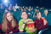 Frontview Of Happy Children Eating Popcorn By Watching Movie. Girl Drinking Fizzy Drink From Red Can poster
