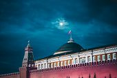 Night Shot Of The Kremlin Moscow Dome Of Senate Building, A Red Kremlin Wall, Flag Of Russia With Th poster