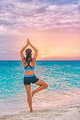 Yoga meditation woman meditating at beach sunset relaxing in yoga posture, tree pose, vrksasana. Rel poster