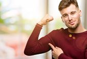 Handsome young man pointing biceps expressing strength and gym concept, healthy life its good poster