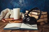 Books Are Stacked, Headphones, White Cup, Orange Slices, Open Diary On A Wooden Background. The Conc poster