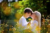 Mother And Son Having Fun. Son Giving Flowers To His Mother And Kissing Her. Outdoor Shot. poster
