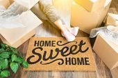 Woman Wearing Sweats Relaxing Near Home Sweet Home Welcome Mat, Moving Boxes and Plant. poster