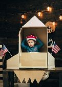 Boy Play With Rocket, Cosmonaut Sit In Usa Rocket Made Out Of Cardboard Box. Kid In Helmet Sit In Ca poster