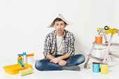 Confused Fun Man In Newspaper Hat Sitting On Floor With Instruments For Renovation Apartment Room Is poster