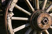 stock photo of wagon wheel  - close up on an old antique wagon wheel - JPG