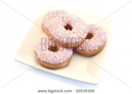 Four Iced Doughnuts With Sprinkles