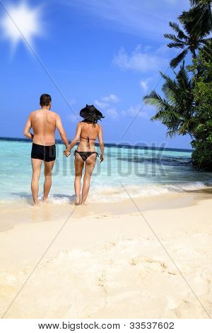 Loving Couple Walking On A Tropical Beach