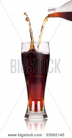 A Bottle Of Cola Soda Pouring Into A Glass Over A White Background With Reflection.