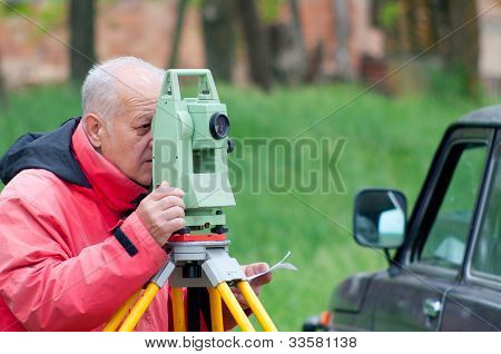 Land surveyor measuring with total station on construction site