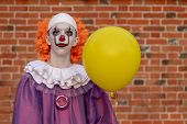 A Guy In A Clown Costume With A Yellow Balloon Against A Brick Wall. Costume For Carnival, All Saint poster