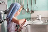 Pretty Young Girl Concentrating On Drying Dishes At The Kitchen Sink poster