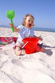 stock photo of baby face  - baby girl exult on the beach in Poland