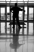 stock photo of average man  - silhouette of a person pausing in their work of mopping an office building floor - JPG