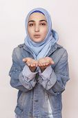 Portrait Of Stylish Muslim Girl In Jean Jacket Sending Air Kiss. Modern And Young Middle-eastern Gir poster