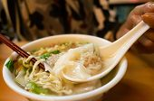 eat wonton noodles with soup on a table poster