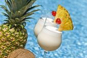 pic of pina-colada  - Two glasses of pina colada garnished with pineapple and maraschino cherry shot in front of a swimming pool - JPG
