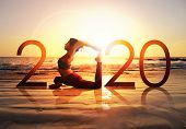 Happy New Year Card 2020. Silhouette Of Healthy Girl Doing Yoga One Legged Pigeon Pose On Tropical B poster