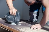 Closeup Hand Of Carpenter, Woodworker With Professional Cutting Tool Fretsaw Or Jigsaw, Cut Wooden T poster
