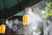 Misting System In The Middle Of Hanoi, Vietnam Cools Down People As They Walk Under The Artificial C poster