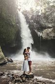 Spanish Couple In Love Kissing With Amazing View Of Waterfall. Happy Together, Honeymoon In Bali. Tr poster
