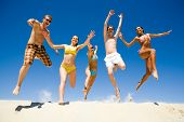 stock photo of party people  - Image of five energetic people jumping at the beach - JPG