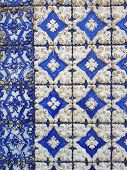 Old Colored Ceramic Tiles. The Wall Is Covered With Blue Tiles With White Patterns. The Relief Patte poster