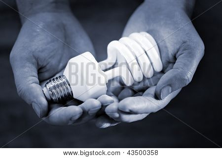 Blue toned monochrome image of hands holding a compact fluorescent bulb. Very short depth-of-field.