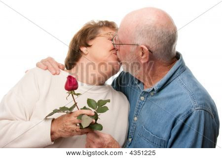 Happy Senior Couple Kissing With Red Rose