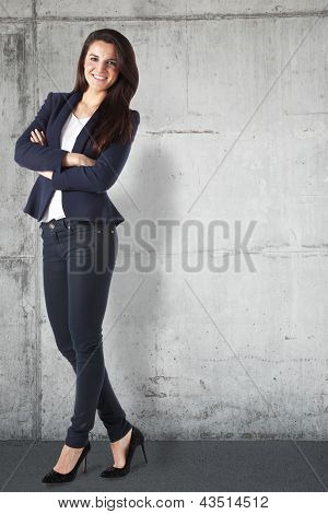 Portrait Of A Beautiful Businesswoman Standing Against Grunge Background