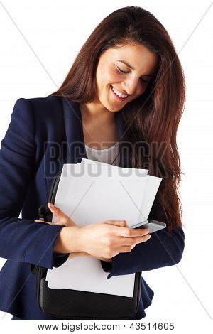 Beautiful Businesswoman With Papers And Sending A Message On Smartphone