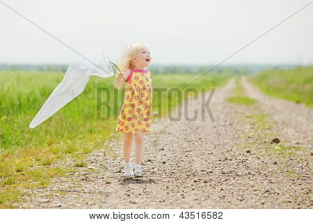 Girl With Butterfly Net Having Fun At Field