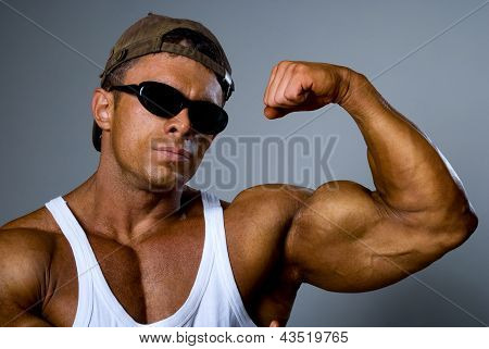 A Strong Man Shows His Muscles. Trained Body. The Gray Background