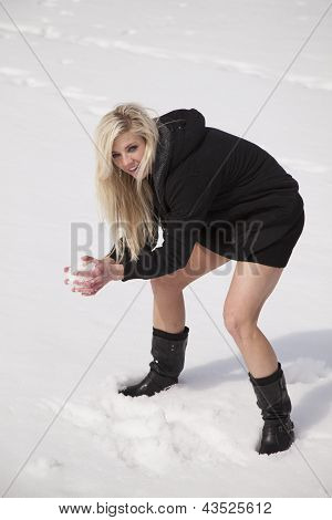 Woman In Black Dress Making A Snowball