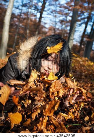 Woman Playing With Autumn Leaves
