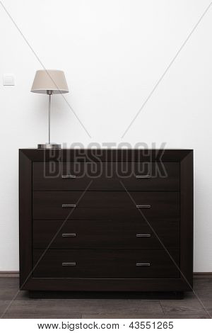 Brown Commode With Lamp In Bright Minimalism Interior