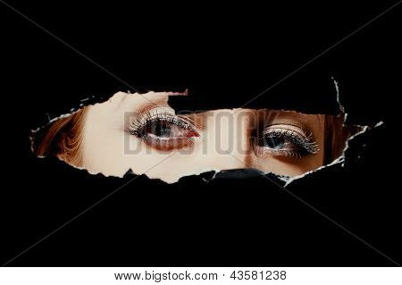 Eyes Of A Young Woman Peeping Through Hole