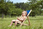 stock photo of lawn chair  - Baby or a toddler child relaxing on a sunbed or a deck chair in a garden - JPG