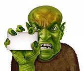 stock photo of ogre  - Monster holding a blank white sign with a zombie or greedy man with a creepy hand holding an ad card as a spooky halloween or scary symbol with textured green skin wrinkled creepy fingers and stitches isolated on white - JPG