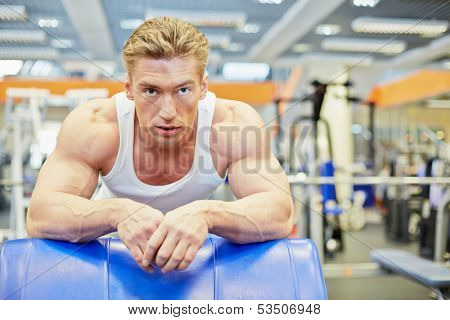 Man gets some rest between exercises in gym hall