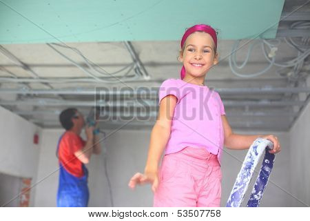 Laughing girl is standing on a stepladder and worker is setting ceiling profile
