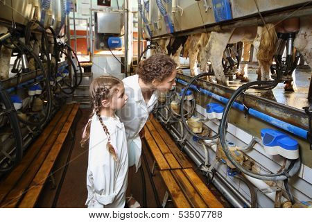 Mother and little daughter in white robes look at machines for milking of cows in big farm.