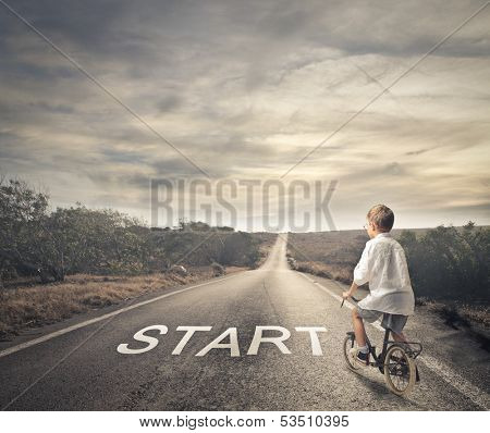 little child pedaling a bicycle on a deserted road