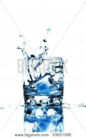 Ice Cube Splashing Into Glass Of Water, Isolated On White