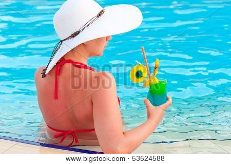 A Girl In A White Wide-brimmed Hat With A Cocktail In The Pool