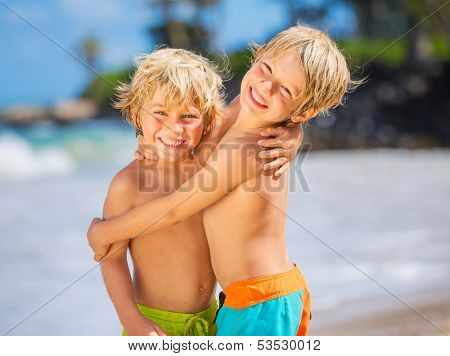 Two young boys having fun on tropical beach, happy best friends playing, friendship concept