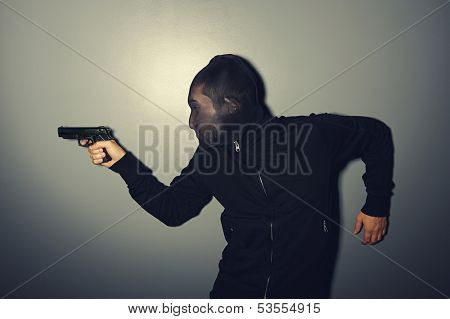 thief with gun stealing over dark wall