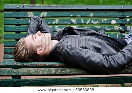 Attractive Blue Eyed, Blond Young Man Laying On Park Bench